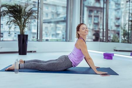 Hatha yoga. Optimistic mature woman smiling while doing yoga asana Stock fotó