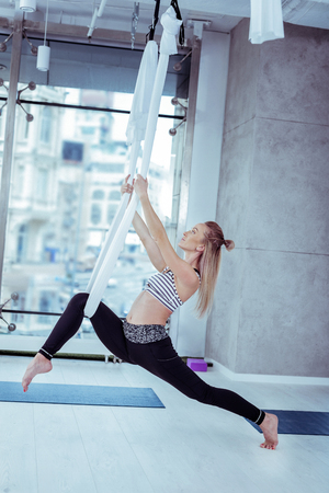 Strengthened muscles. Attractive successful woman finding correct alignment in pose and using hammock Stock fotó