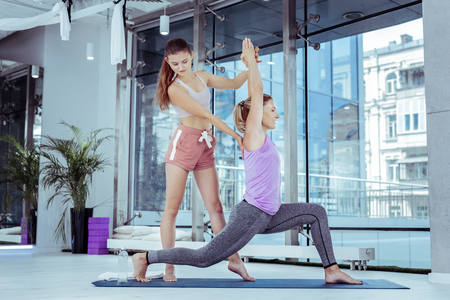 Yoga challenge. Focused female trainer correcting woman who doing yoga poses