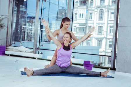 Benefits from yoga. Merry mature woman doing asana while trainer holding her hands Stock fotó