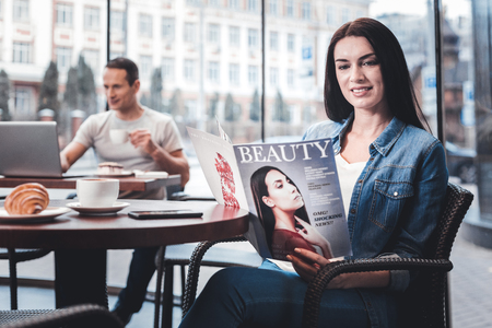 Press review. Attractive female holding magazine while sitting in cafe and having coffee break