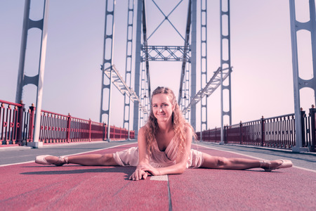 Great mood. Joyful female dancer smiling to you while doing splits