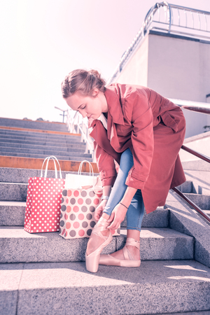 After shopping. Nice beautiful ballerina fixing her shoes while standing near her shopping bags