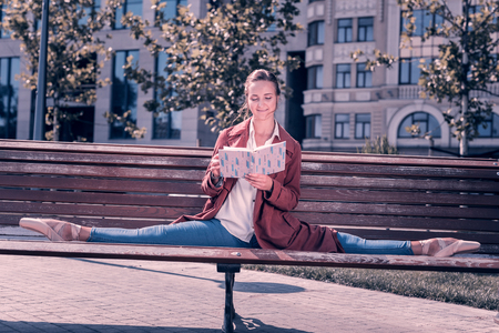 Pleasurable time. Smart young ballerina doing the splits on the bench while reading a book in the park