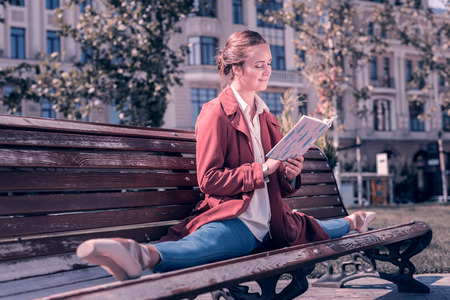 My hobby. Joyful positive ballerina holding a book while reading it in the park