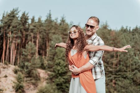 Secret hideaway. Beaming happy loving couple wearing nice sunglasses enjoying their secret hideaway in the forest