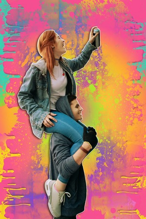 Funny activity. Positive young street artist laughing while holding spray paint and sitting on the shoulders of her strong boyfriend