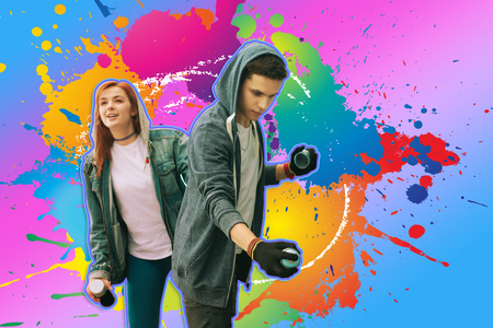 Creative teenagers. Careful teenager holding spray paint and creating graffiti while his girlfriend looking into the distance