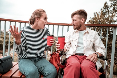 Hot coffee. Attentive calm disabled man holding cup of coffee and looking at his emotional friend while listening to her