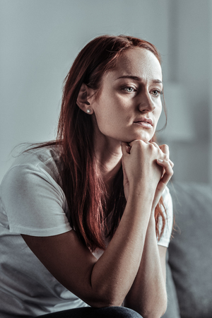 Taking decision. Negative delighted female person sitting on the couch and touching chin while looking forward
