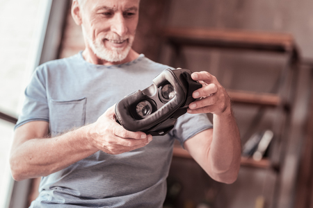 Powerful tool. Close up of virtual reality mask being kept in hands of joyful bearded man