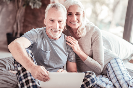 Happiness. Portrait of elderly family sitting close to each other while looking at you and smiling Stock Photo