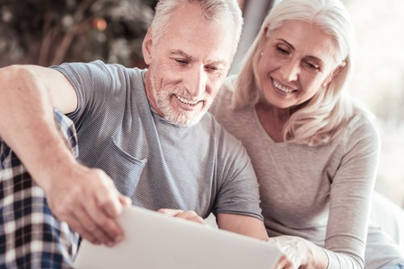 Expressing interest. Close up of positive elderly couple looking at the laptop screen while sitting together and smiling