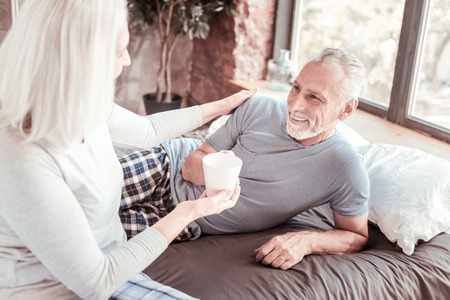 Good morning. Portrait of cheerful wife bringing a cup of tea for her husband while touching his shoulder and smiling Stock Photo