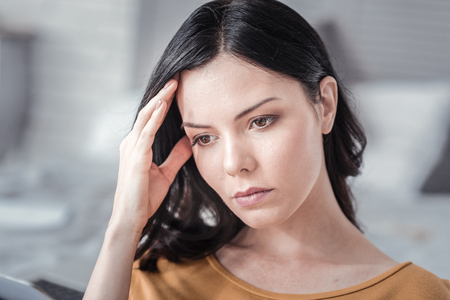 So concentrated. Thoughtful female bowing her head and looking downwards while suffering from headache Stock Photo