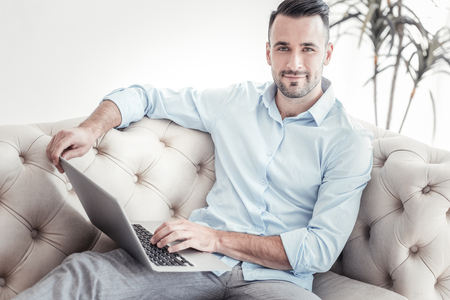 Work everywhere. Attractive male person sitting on cozy couch and keeping laptop on knees while looking straight at camera