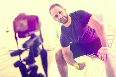Home training. Pleasant attractive man feeling confident while posing in front of the camera