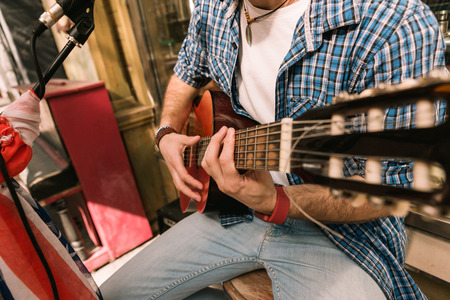 Feel music. Close up of handsome male hands playing on guitar and practicing skills