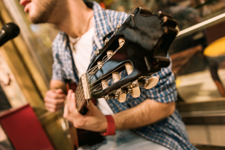 Feel sound. Close up of shiny wooden headstock and man singing and playing guitar Reklamní fotografie