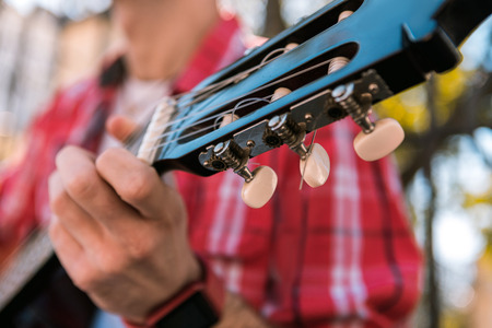 Elegant headstock. Close up of brown headstock and male hand touching guitar and playing for pleasure