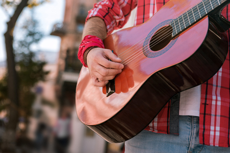 Music business. Close up of male handsome hand strumming strings and producing song on guitar