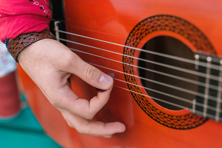 Wonderful melody. Close up of male tender hand holding mediator and picking strings Archivio Fotografico