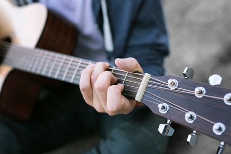 Playing the guitar. Close up of young boy wearing jeans and blue sport jacket playing the guitar being fond of music greatly