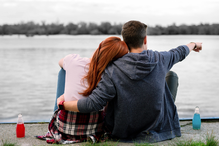 Hugging girlfriend. Dark-haired boyfriend feeling memorable while hugging his girlfriend sitting near river and drinking alcohol Banco de Imagens - 110126871