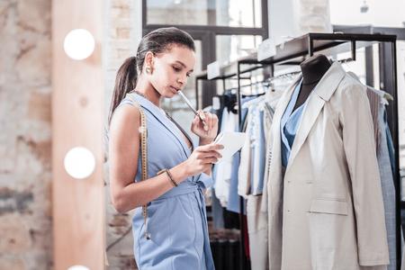 Unsure designer. Beautiful professional fashion designer wearing stylish elegant vest feeling unsure about choosing fabrics