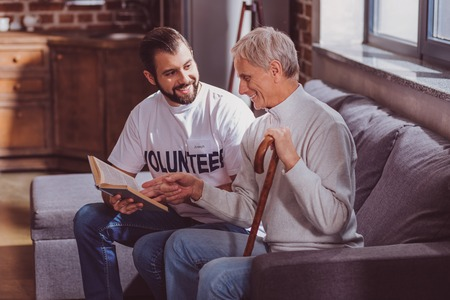 Avid readers. Glad bearded volunteer reading a book for the aged man and smiling