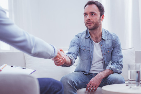 Problem being solved. Satisfied bearded man shaking hands with his personal experienced psychiatrist while sitting on sofa and looking in doctors eyes