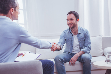 Gratitude. Pleased positive bearded man shaking hands with professional psychiatrist while being extremely thankful to him for a high quality assistance Stock Photo