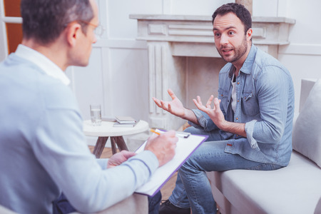 Much information to tell. Excited enthusiastic bearded man explaining his personal problems to psychologist while sitting on sofa and gesticulating