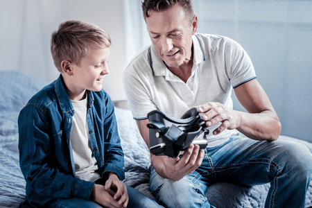 Adult toy. Interested joyful attentive man sitting in the bright room near his son holding and demonstrating the VR glasses. Фото со стока