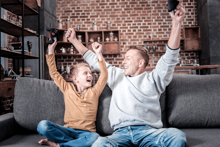 We are the champions. Happy satisfied friendly natives sitting on the sofa holdings gamepads and rejoicing. Stock Photo
