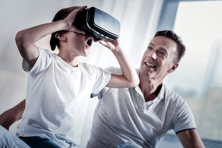 New experience. Amazed little surprised boy sitting in the bright room near his father examining the VR glasses opening his mouth.