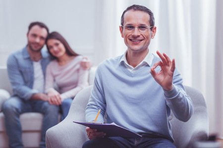 Portrait of cheerful experienced psychologist making a circle with thumb and pointer finger while his satisfied clients embracing on background