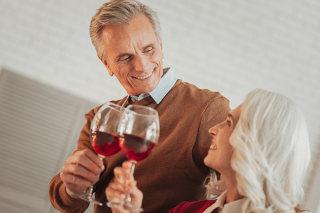 Happy smiling elderly couple celebrating anniversary and looking into each others eyes while holding glasses of red wine