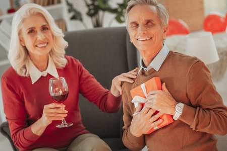 Joyful smiling senior man keeping his eyes closed and pressing a gift to his chest while gorgeous woman beside touching his shoulder and holding a glass of wine