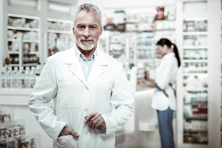 Senior pharmacist wearing white coat coming to the drugstore checking the work of his employees