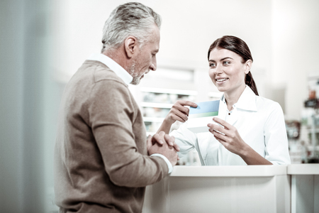 Pleasant cheerful dark-haired pharmacist talking to her grey-haired client asking some questions