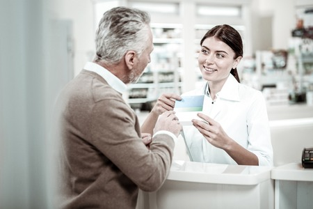 Bearded grey-haired customer coming to pharmacy store buying some medicine for his family
