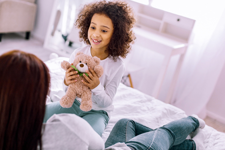 Joyful child sitting on bed and looking at her young mother