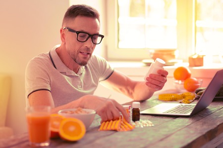 Careful concentrated man choosing vitamins while being in a room