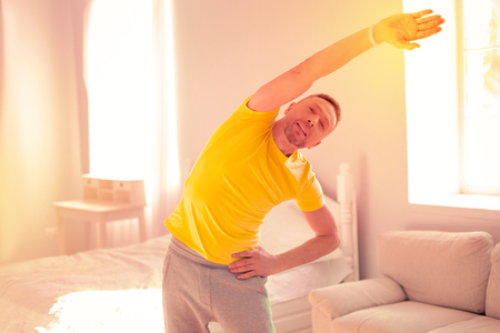 Purposeful nice man smiling while doing exercises Stock Photo