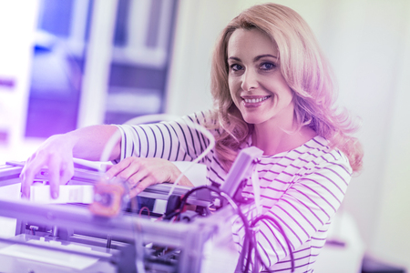 Smiling blonde-haired office worker inserting new cartridge into laser printer while printing new sketches