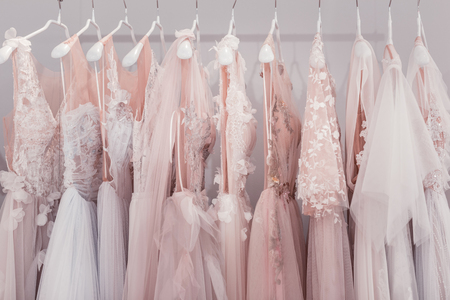 Wedding dresses hanging together in the wedding boutique while waiting for someone to buy them