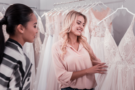 Nice happy women looking at a dress while visiting a wedding boutique