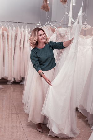 Joyful positive woman smiling while finding a perfect wedding dress 免版税图像