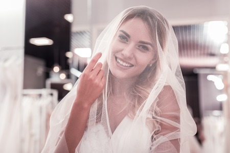 Nice positive woman looking at you through the veil while wearing a wedding dress Stock fotó